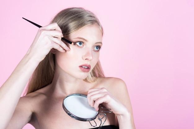 Mooi meisje dat cosmetica aanbrengt met eyeliner sexy meisje met lang blond haar dat potlood aanbrengt voor