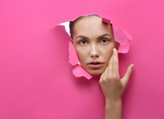Mooi meisje dat door verscheurd gat in stijve roze karton kijkt.
