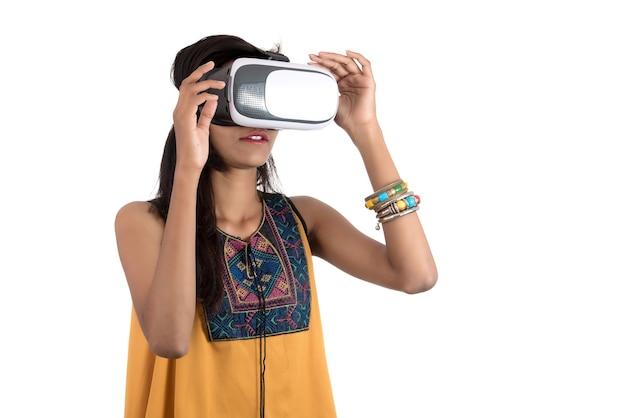 Mooi meisje dat door vr-apparaat kijkt. jong meisje dat de hoofdtelefoon van de virtuele werkelijkheidsbril draagt.
