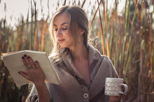 Mooi meisje dat een boek in de herfstbos leest