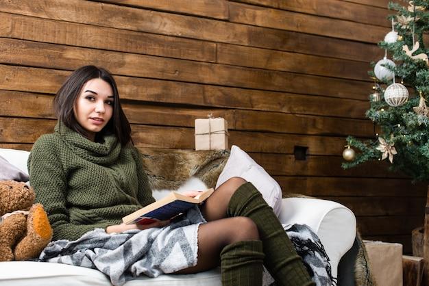 Mooi meisje dat een boek in een kerstmisatmosfeer leest