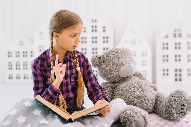 Mooi meisje dat een boek met haar teddybeer leest