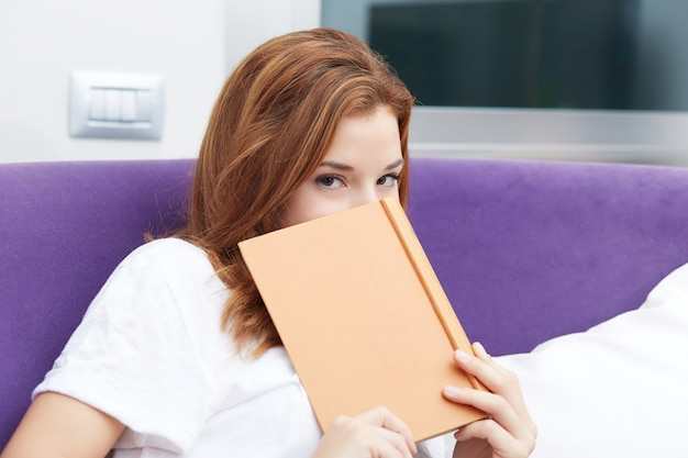 Mooi meisje dat een boek op purpere bank leest