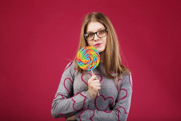 Mooi meisje dat een bril draagt die grote gestreepte lolly houdt