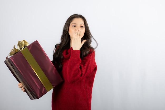 Mooi meisje dat een kerstcadeau vasthoudt en een luchtkus blaast.