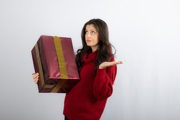 Mooi meisje dat een kerstcadeau vasthoudt en omhoog kijkt.