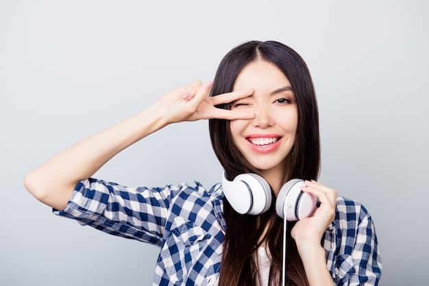 Mooi meisje dat een knipoog geeft die vsign-slijtagehoofdtelefoons toont