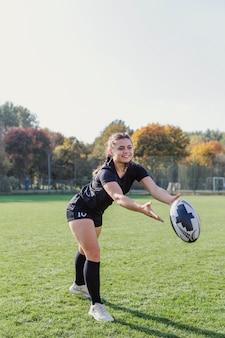 Mooi meisje dat een rugbybal vangt