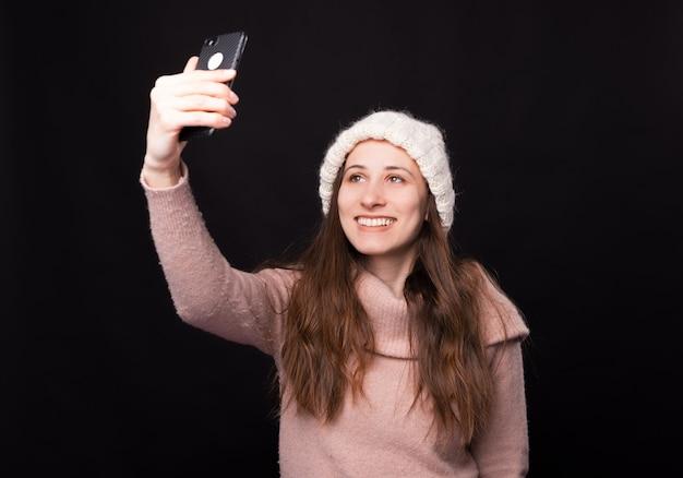 Mooi meisje dat een selfie met haar telefoon maakt op zwarte achtergrond.