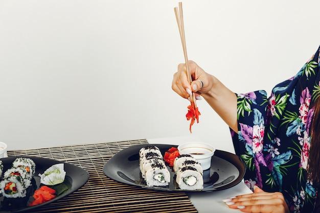 Mooi meisje dat een sushi in een studio eet