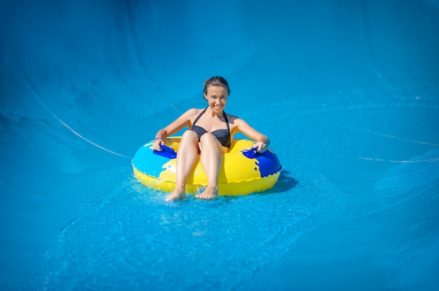 Mooi meisje dat een waterglijbaan berijdt