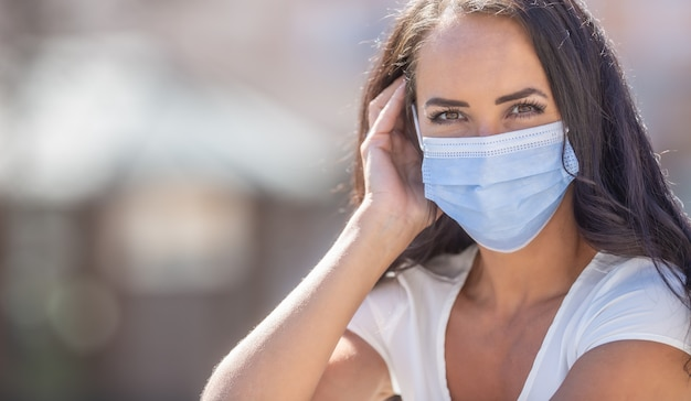 Mooi meisje dat een wegwerpmasker draagt en in de camera kijkt tijdens de uitbraak van het coronavirus.