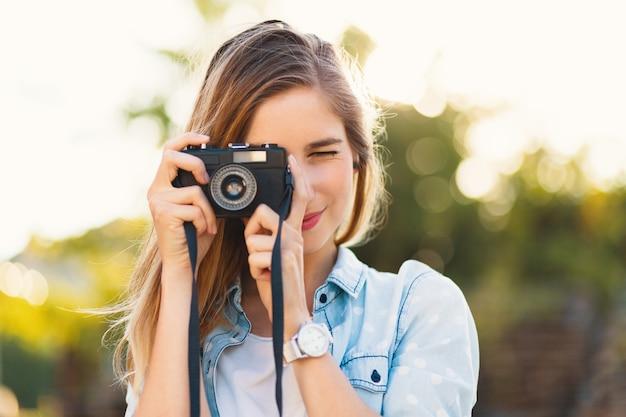 Mooi meisje dat foto's met een uitstekende camera op een zonnige dag neemt