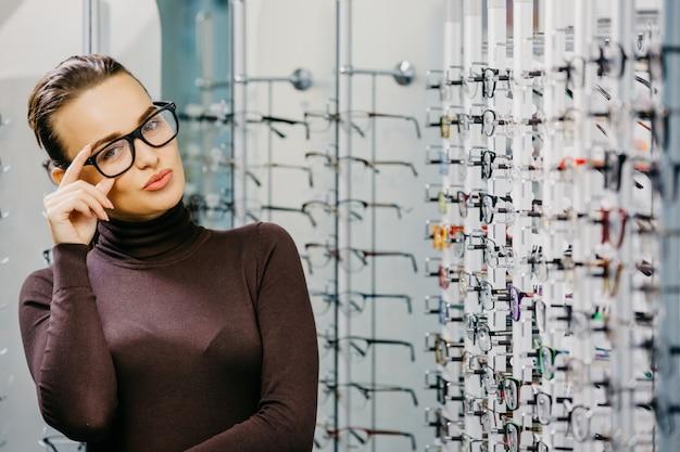 Mooi meisje dat glazen in optische winkel draagt