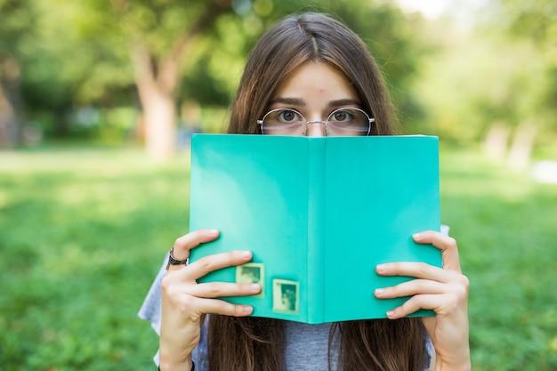 Mooi meisje dat haar gezicht behandelt met boekonderwijs en de selectieve nadruk van het mensenconcept.