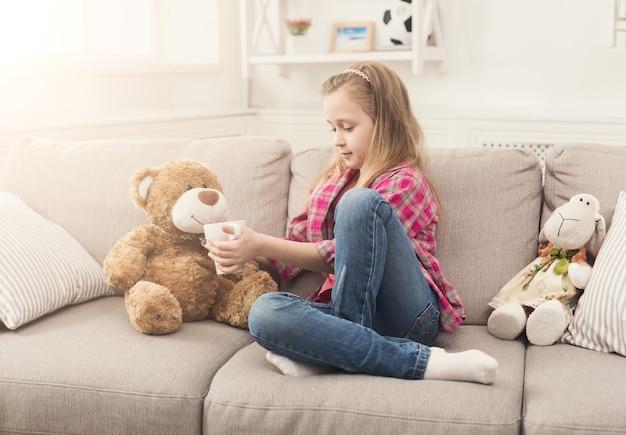 Mooi meisje dat haar teddybeer behandelt met thee. schattige vrouwelijke jongen spelen op de bank thuis met speelgoed. vrije tijd en tijdverdrijf voor kinderen, kopieer ruimte
