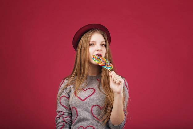 Mooi meisje dat hoed draagt die grote gestreepte lolly bijt