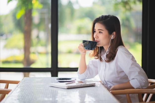 Mooi meisje dat in de koffie werkt en wat koffie drinkt