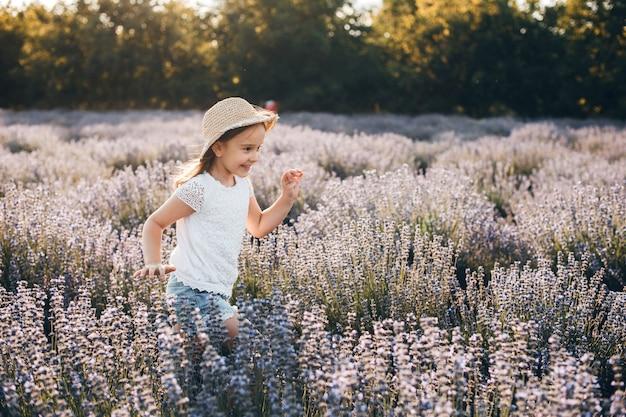 Mooi meisje dat in een gebied van bloemen loopt dat tegen zonsondergang lacht die een hoed draagt.