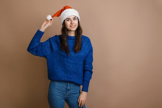 Mooi meisje dat in rode santa claus-hoed op bruine achtergrond gelukkig en opgewekt kijkt. fijne feestdagen voor kerstmis en nieuwjaar.