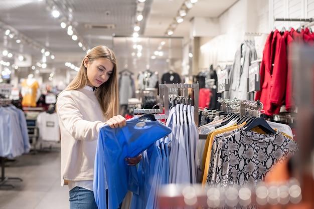 Mooi meisje dat in vrijetijdskleding een nieuw overhemd kiest in de kledingafdeling van een groot modern winkelcentrum of handelscentrum