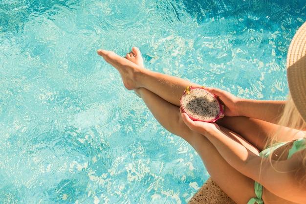Mooi meisje dat in zwembad draakfruit eet