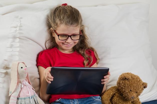 Mooi meisje dat met glazen op haar tablet let