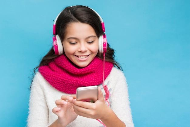 Mooi meisje dat met hoofdtelefoons smartphone bekijkt