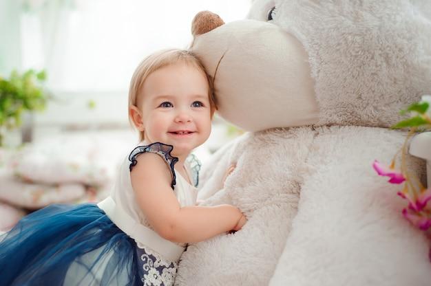 Mooi meisje dat met stuk speelgoed bij de camera glimlacht
