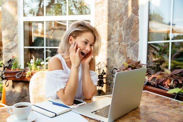 Mooi meisje dat met wonder laptop scherm bekijkt, dat in openlucht zit