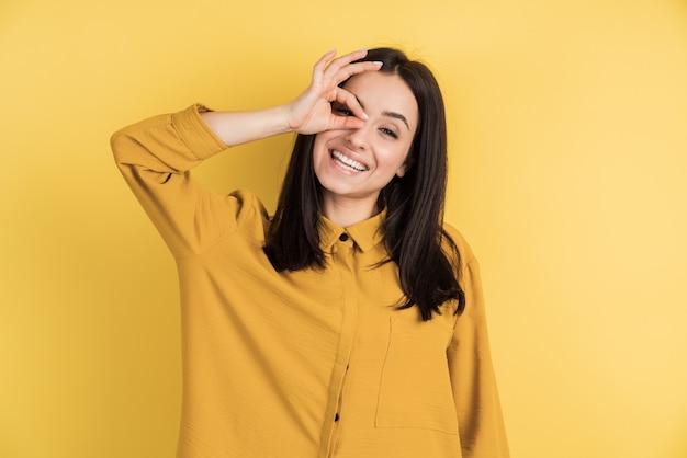 Mooi meisje dat ok tekenadvertentieoplossing goede die keus toont die op gele muur wordt geïsoleerd