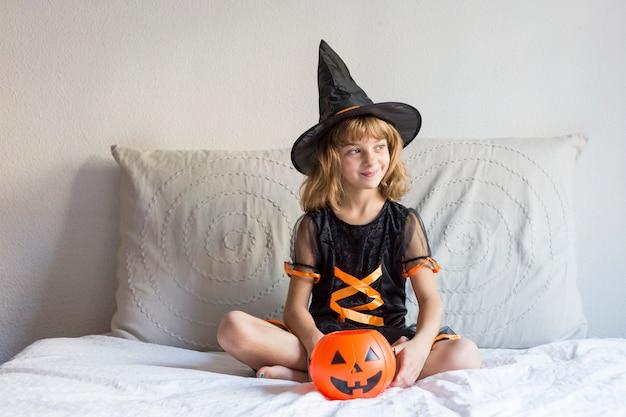 Mooi meisje dat op bed glimlacht en een halloween-kostuum draagt. spelen met pompoenen