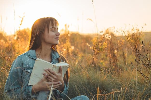 Mooi meisje dat op de herfstgebied een boek leest. het meisje, zittend op een gras, een boek lezen. rust en lees. buiten lezen.