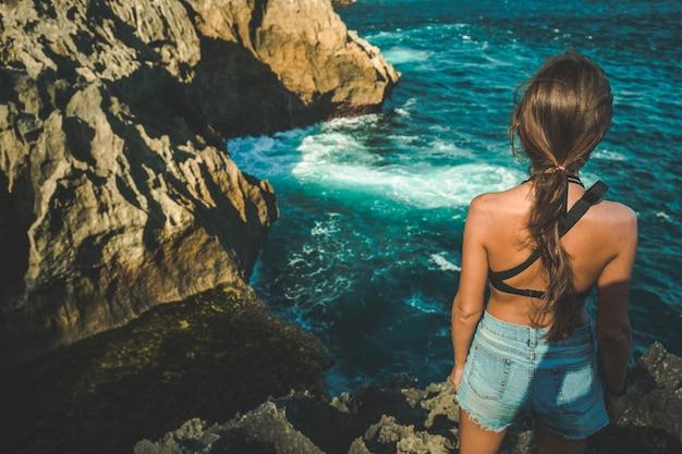 Mooi meisje dat op de rand van een klif in de buurt van de oceaan staat, achteraanzicht gebroken strand is prachtig