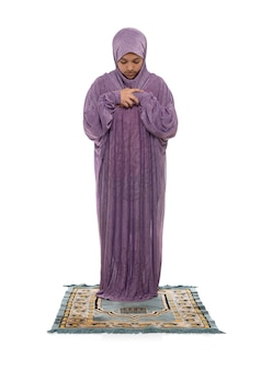 Mooi meisje dat op een mat bidt