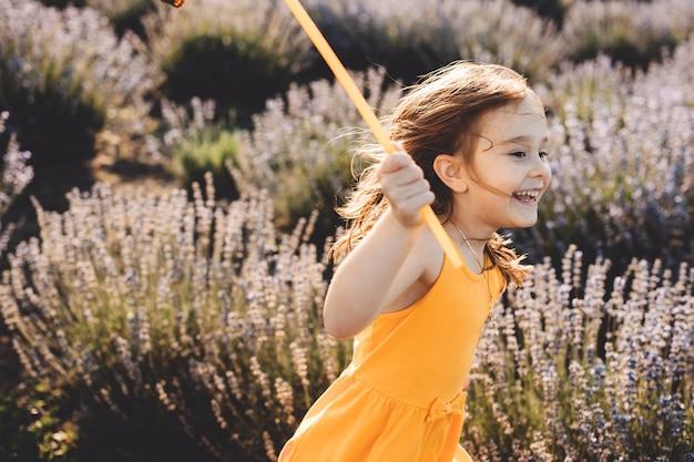 Mooi meisje dat op gebied van bloem loopt, gekleed in gele kleding tegen zonsondergang.