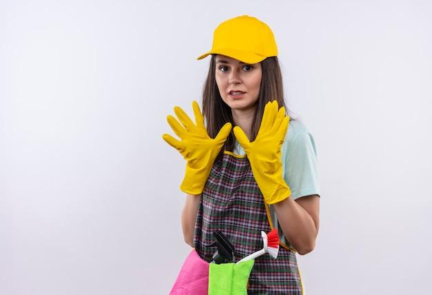 Mooi meisje dat schort, glb en rubberhandschoenen draagt die defensiegebaar met bang handen maken