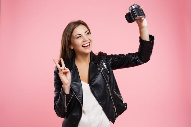 Mooi meisje dat selfie op oude rolfilmcamera neemt