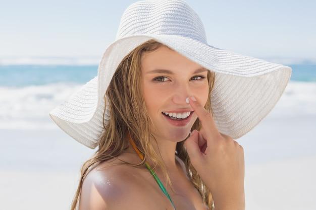 Mooi meisje dat spf op neus op het strand zet dat bij camera glimlacht