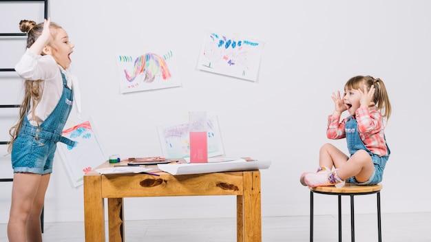 Mooi meisje dat stellend meisje op stoel schildert