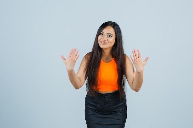 Mooi meisje dat stopgebaar in oranje bovenkant, rok toont en vrolijk kijkt. vooraanzicht.