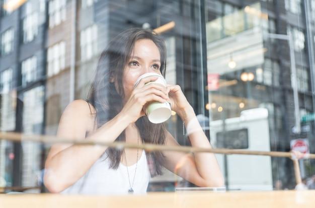 Mooi meisje dat van een hete koffie binnen een winkel in new york geniet