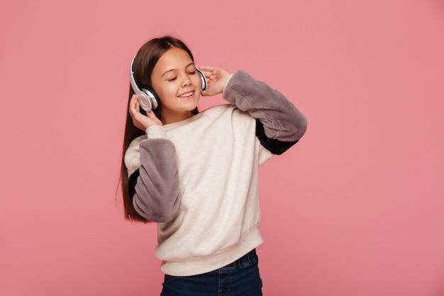 Mooi meisje dat van geïsoleerde muziek in hoofdtelefoons geniet