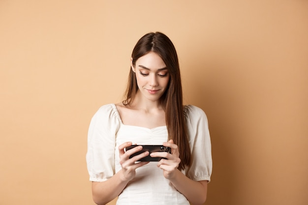Mooi meisje dat video's bekijkt op een smartphone die de mobiele telefoon horizontaal houdt en naar het scherm kijkt...
