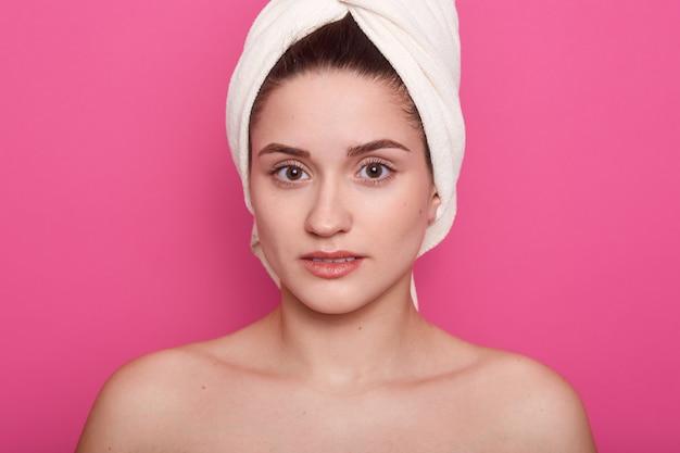 Mooi meisje dat witte handdoek op hoofd draagt, die met ontblote schouders stelt die op roze studio wordt geïsoleerd, aantrekkelijke dame die direct camera bekijkt, die schone perfecte huid heeft. skinncare concept.
