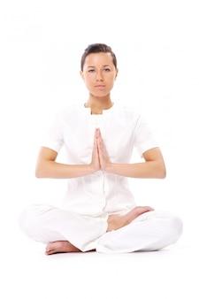Mooi meisje dat yogaoefeningen op wit doet