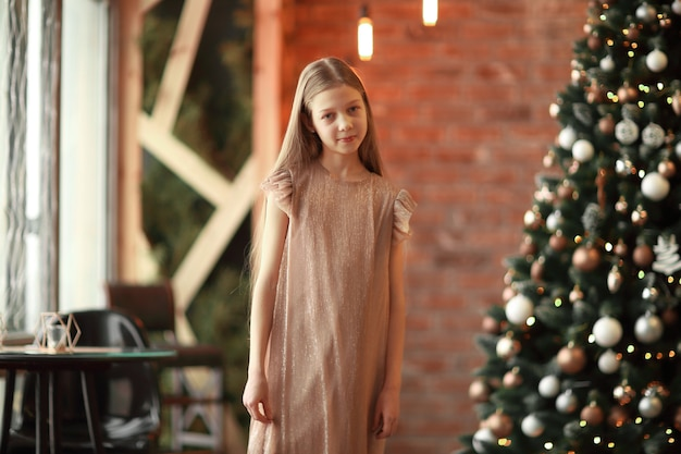 Mooi meisje dat zich bij de kerstboom bevindt