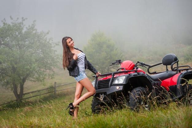 Mooi meisje dat zich dichtbij atv met vier wielen bevindt