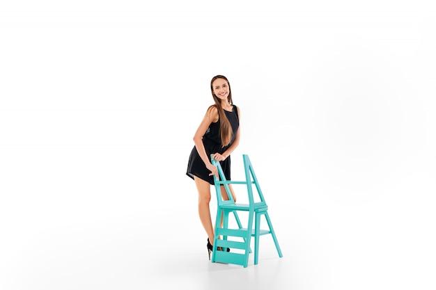 Mooi meisje dat zich dichtbij vouwende die trapladderstoel bevindt op wit wordt geïsoleerd