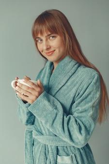 Mooi meisje dat zich in een blauwe badjas bevindt